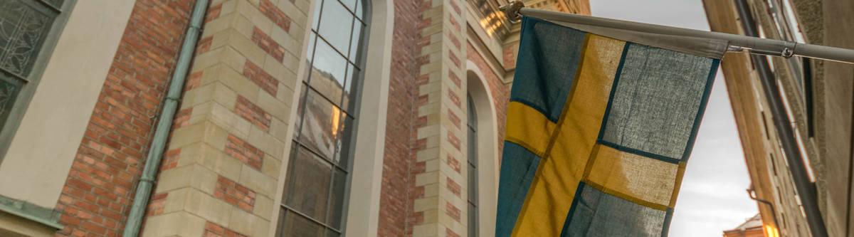 De Zweedse vlag in een pitoresk steegje in Stockholm.